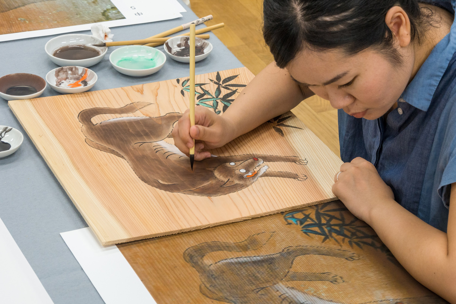 A student at the Tokyo University of the Arts reproduces one of the ceiling paintings of wolves at Yamatsumi Shrine in Fukushima Prefecture that has been destroyed by fire.   MICHIKO HAYASHI